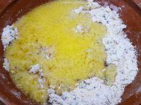 1 - Couper les carambars en petits morceaux et les passer au mixeur, réserver. Verser la farine dans une jatte, y ajouter la cassonade et la poudre d'amande, mélanger. Faire un puits au centre du mélange, y casser l'oeuf et verser la vanille liquide. Bien mélanger le tout pour obtenir un sable grossier. Incorporer les carambars mixés, mélanger. Verser ensuite le beurre fondu et pétrir afin d'obtenir une pâte homogène. Mettre au réfrigérateur pour un temps de repos de 30 mn.