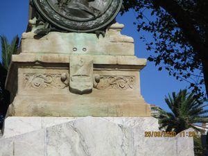Le monument aux morts, son sommet est conçu d'un ornement à tour crénelée aux armoiries de la ville, à tête de résistance sculptée d'une guirlande végétale où s'entremêle des feuilles de laurier et de palme ornées d'un médaillon en bronze représentant le profil d'André Rocaries coiffé d'une baratine maire de 1793.