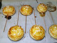 2 - Placer sur une plaque allant au four recouverte de papier sulfurisé.  Recouvrir du 2ème disque de pâte. Souder les bords à l'aide d'une fourchette. Renouveler l'opération pour les autres oreillons.  Dorer au pinceau avec du jaune d'oeuf battu délayé dans un peu d'eau, parsemer de grains de sucre blanc. Enfourner pour 10 mn environ th 6 jusqu'à ce que la pâte soit bien gonflée et dorée. Sortir du four et laisser refroidir. Présenter ensuite vos pie pops sur une assiette de service en réalisant une belle décoration.