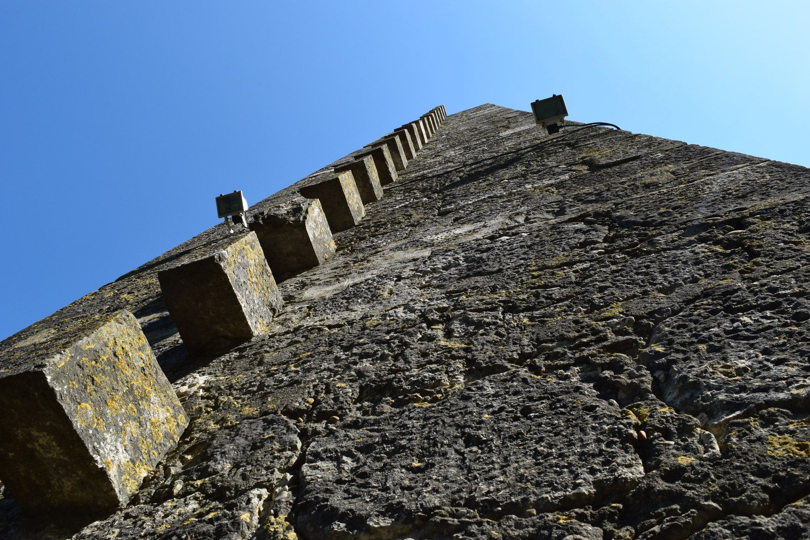 Sa face ouest présenteencore les pierres en boutisse* servant à l'escalier. (*BOUTISSE. Pierre dont la longueur se trouve dans l'épaisseur du mur et dont un des bouts est en parement.)
