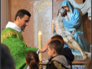 Les catéchumènes sont marqués du signe de la croix par le père Marc et reçoivent la Parole de Dieu