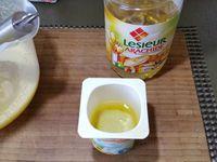 1 - Mettre le four à préchauffer th 6. Dans un récipient, casser les oeufs. Vider le yogourt dans un bol et utiliser le pot pour mesurer le sucre. Battre les oeufs et le sucre au fouet à main jusqu'à ce que le mélange blanchisse et soit mousseux. Récupérer le zeste d'un citron et ajouter au mélange. Incorporer à la préparation la moitié d'un pot d'huile d'olive et une autre moitié d'huile d'arachide.