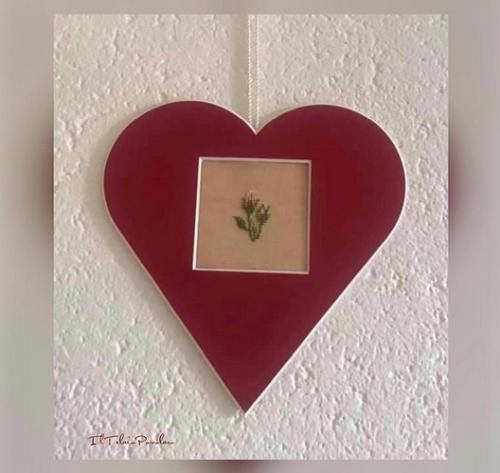 Boccioli di rosa in un cuore passpartout rosso