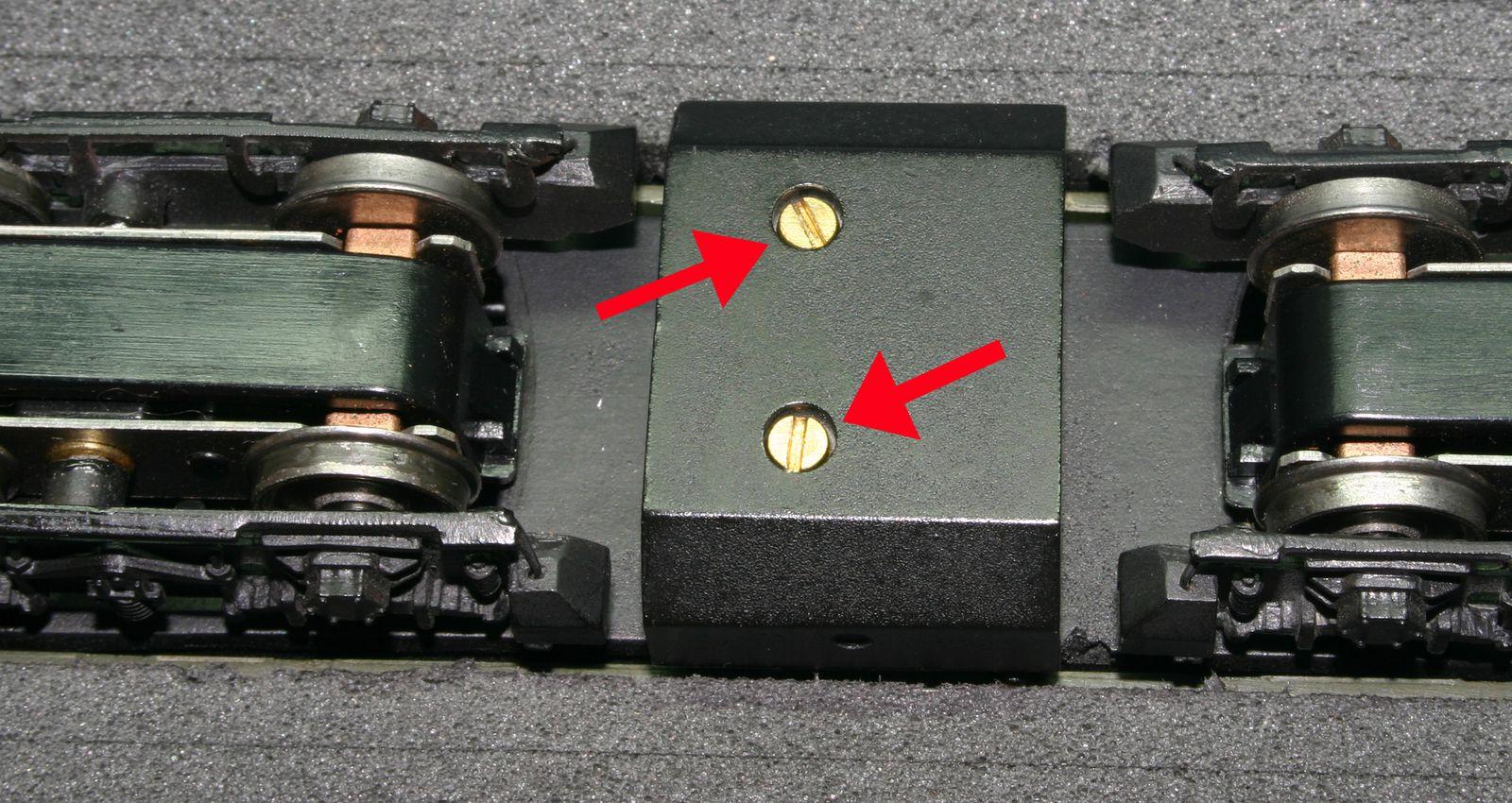 3 ème opération je dois isoler du chassis la conexion sous le moteur  en intercalant une bande de carton entre ceux -ci. Pour cela je dévisse les 2 vis de maintien du réservoir puis les 4 vis de fixation de moteur.