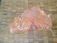 3 - Couper les 4 tranches de saumon fumé en lanières. En garder une pour la décoration et répartir les 3 autres sur le fond de tarte. Recouvrir de la préparation au fromage, puis disposer joliment dessus vos rondelles de concombre, de tomates et tranches d'avocat, placer au centre en chiffonnade les lanières de saumon fumé. Faire griller à sec à la poêle ou au four les pignons de pin et ciseler la ciboulette fraîche.