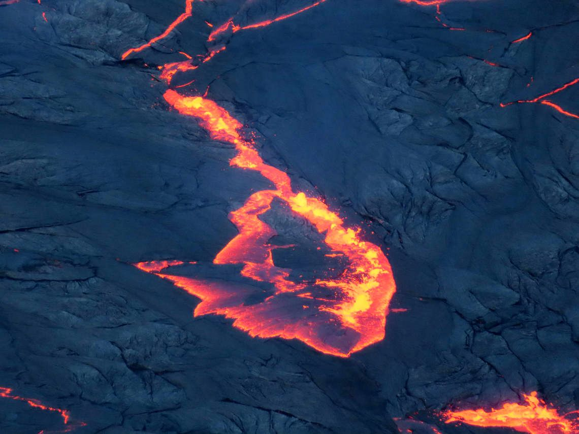 A telephoto view of a slump in the active lava lake in Halema'uma'u Crater, atop Kīlauea. Melting occurs when the colder, denser, solidified crust (black) sinks under less dense liquid lava (orange). Photo taken at 7:48 a.m. HST on October 4, 2021. USGS photo by J.M. Chang.