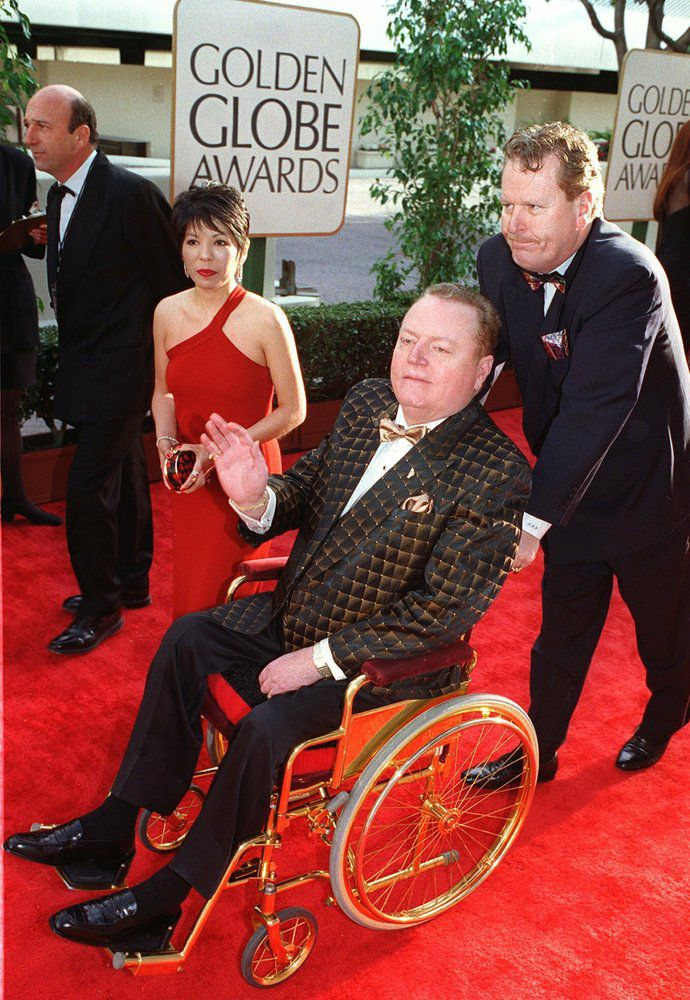 "FILE - ""Hustler"" magazine publisher Larry Flynt arrives in a wheelchair for the 54th annual Golden Globe Awards on Jan. 19, 1997, in Beverly Hills, Calif. Flynt, who turned ""Hustler"" magazine into an adult entertainment empire while championing First Amendment rights, has died at age 78. His nephew, Jimmy Flynt Jr., told The Associated Press that Flynt died Wednesday, Feb. 10, 2021, of heart failure at his Hollywood Hills home in Los Angeles. (AP Photo/Chris Pizzello, File)"