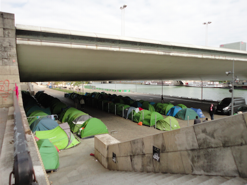 Migrants tents lined up under a bridge