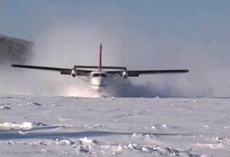 Twin Otter landing frozen lake with wheel-skis