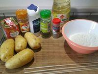 1 - Bien laver et sécher les pommes de terre. Huiler les piques en bois, les enfoncer au cente des pommes de terre dans la longueur. Avec un couteau bien aiguisé, inciser les pommes de terre en les faisant pivoter de façon à les découper en spirale comme sur les photos.