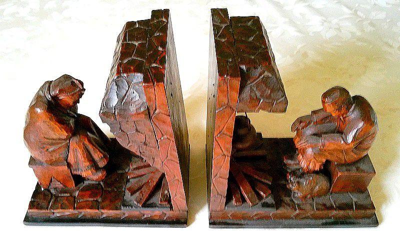 Paire de serre-livres en bois sculptés couple de paysans avec chat devant cheminée.