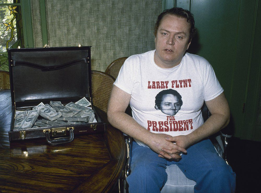 "FILE - Publisher of ""Hustler"" magazine Larry Flynt is seen with a briefcase full of cash on Oct. 27, 1983, in Los Angeles. Flynt, who turned ""Hustler"" magazine into an adult entertainment empire while championing First Amendment rights, has died at age 78. His nephew, Jimmy Flynt Jr., told The Associated Press that Flynt died Wednesday, Feb. 10, 2021, of heart failure at his Hollywood Hills home in Los Angeles. (AP Photo/Wally Fong, File)"