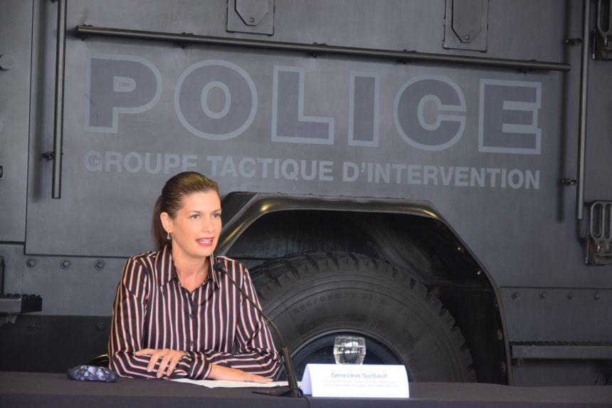 Geneviève Guilbault intimida y amenaza frente a un enorme vehículo policial oscuro.Un poco más y viene vestida con camisa de prisionera.