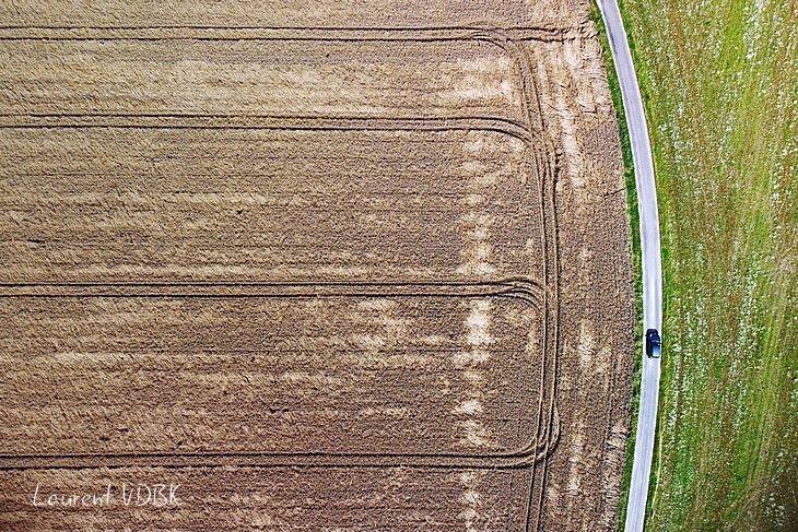 Route qui borde un champ moissoné, où les traces des roues des tracteurs forment des lignes paralléles, vu de haut (drone)