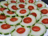 2 - Disposer joliment les rondelles de concombre au coeur de tomates cerises dans une assiette, Décorer de quelques olives noires dénoyautées et saupoudrer de piment d'Espelette.