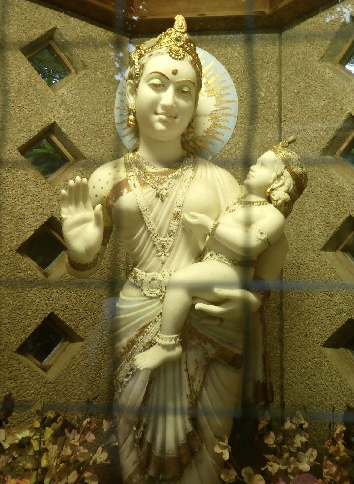 """Statue de Maya et l'enfant Bouddha que l'on peut apercevoir à travers les fentes et le grillage d'une espèce de """"cabine téléphonique"""" à gauche de l'escalier montant vers le temple"""