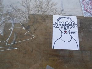 """Des petits dessins de la taille d'une carte de métro apposés sur des fenêtres, avec le label """"art"""" en calligraphie hébraïque."""
