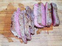 2 - Ecraser l'ail avec le plat du couteau. Dans un bol, verser les huiles, ajouter l'ail écrasé, les feuilles de laurier. Brancher la plancha ou le grill. Badigeonner généreusement sur chaque face les pavés de rumsteak d'huile aromatisée à l'aide de la branche de romarin. Puis bien les assaisonner de chaque côté avec la marinade sèche. Saisir la viande sur le grill, la plancha ou au barbecue sur chaque face selon la cuisson désirée.  Laisser reposer 2 mn, puis couper en tranches. Rajouter de la marinade sèche, poivrer et servir de suite avec des légumes grillés ou l'accompagnement de votre choix.