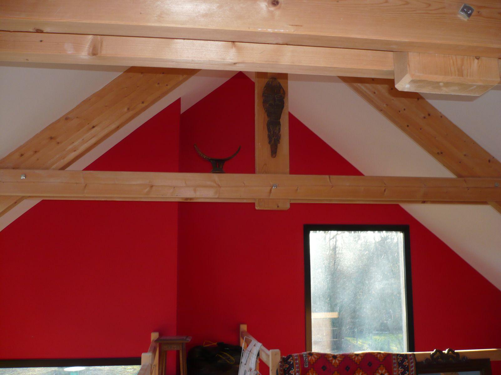 La couleur rouge réchauffe la pièce et s'allie parfaitement avec le bois. Le blanc fait ressortir le mur pour le mettre en valeur.