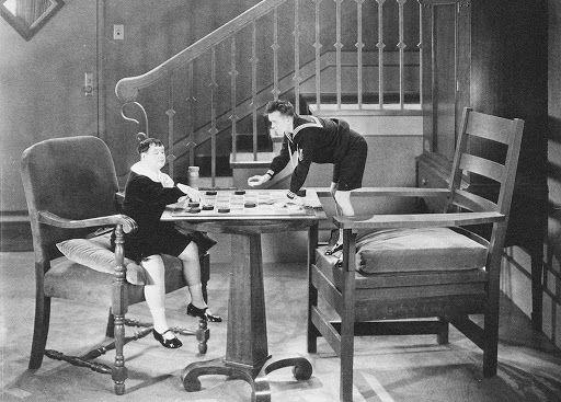 """Laurel et Hardy jouent aux dames au milieu d'un mobilier géant dans """"Les bons petits diables"""" (1930)"""