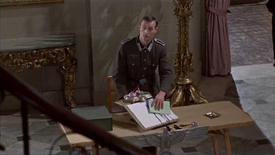 L'allemand à l'entrée garde l'oeil sur Reisman et Wladislaw et cela sur plusieurs scènes.