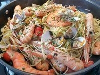 2 - Verser un bon filet d'huile d'olive dans un sauteuse. Faire revenir 1 mn les fruits de mer (langoustines et gambas). Rajouter l'ail (2 gousses), remuer, puis verser le jus de cuisson des coques, mélanger, ajouter les coques et tellines (en garder quelques unes pour la décoration). Rajouter les tomates cerises, les câpres, mélanger et incorporer les linguine en remuant, laisser réchauffer sur le feu 2 à 3 mn. Décorer du reste de coquillages et parsemer de persil haché. Présenter directement dans la sauteuse en rajoutant sur le dessus des pâtes les 4 cuil.à soupe de crème fraîhe, ou en parts individuelles dans des assiettes préalablement chauffées avec 1 cuil.à soupe de crème fraîche par plat. Déguster de suite accompagné éventuellement d'un vin italien.