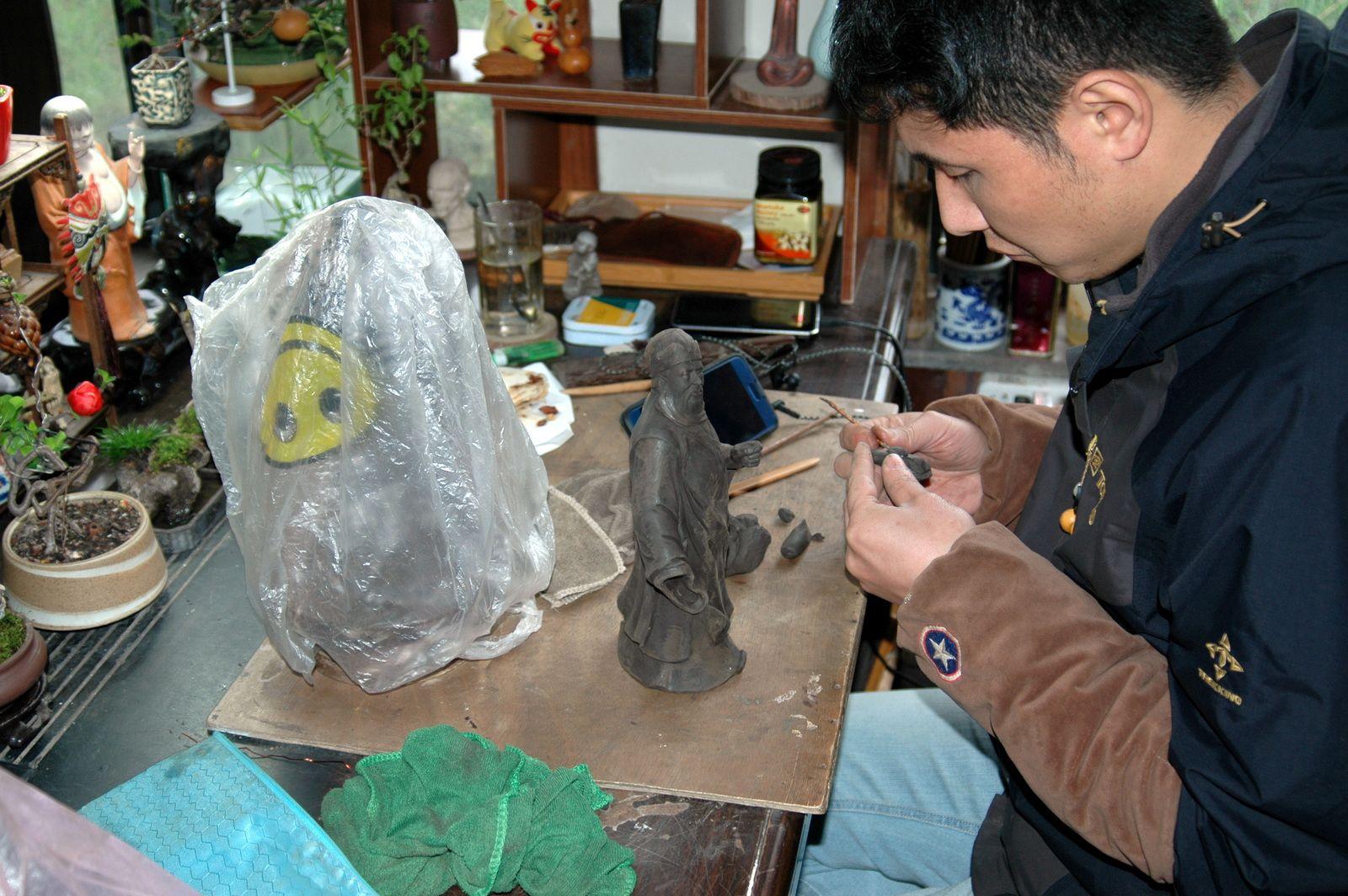 L'artiste qui réalise la base en argile