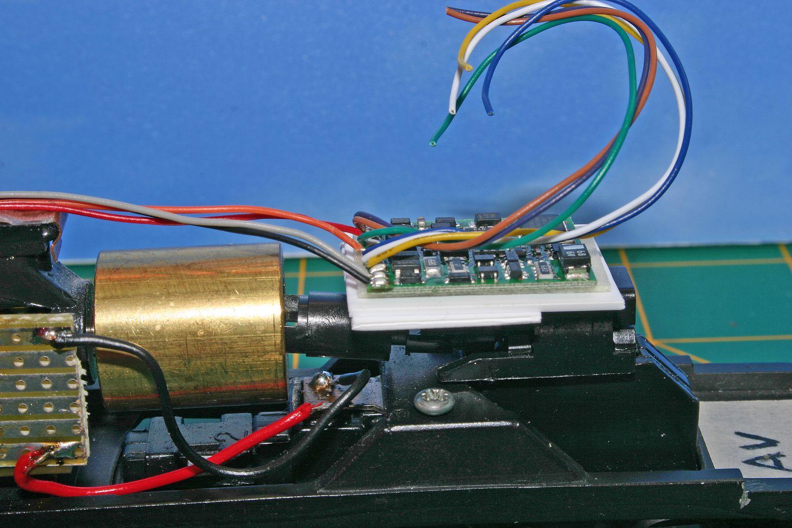5ème opération;cablâge du décodeur collé sur son support.Les fils rouge,noir, orange et gris sont soudé sur la plaque cuivrée en correspondance avec les fils précédament soudés. Un test sur mon diorama permet un contrôle du bon fonctionnement du décodeur.