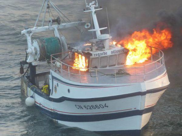 """Le chalutier """"Regarde Ailleurs"""", en proie à un incendie, a fini par sombrer au large de la Pointe du Hoc - photo : Marine Nationale"""