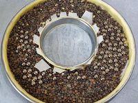 1 - Mettre le four à préchauffer th 6. Déposer une feuille de papier sulfurisé sur une plaque allant au four et disposer au centre le cercle de 24 cm de diamètre. Etaler la pâte brisée la déposer sur le cercle, bien foncer la pâte sur le fond et les rebords puis venir ôter l'excédent de pâte avec un rouleau à pâtisserie. Placer le petit cercle au centre et utiliser comme emporte-pièce pour retirer le rond central de pâte. Se servir de l'excédent de pâte pour réaliser une bande à la dimension du petit cercle et venir l'entourer sur celui-ci (préalablement légèrement huilé), bien souder cette bande au fond de tarte. Découper une feuille de papier sulfurisé pour placer sur la couronne et ses bords. Répartir les billes ou légumes secs et enfourner th 6 pour une cuisson à blanc pendant 20 à 25 mn.