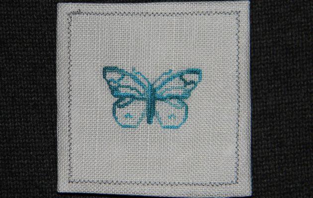 Petite broderie papillon sur toile de lin grise