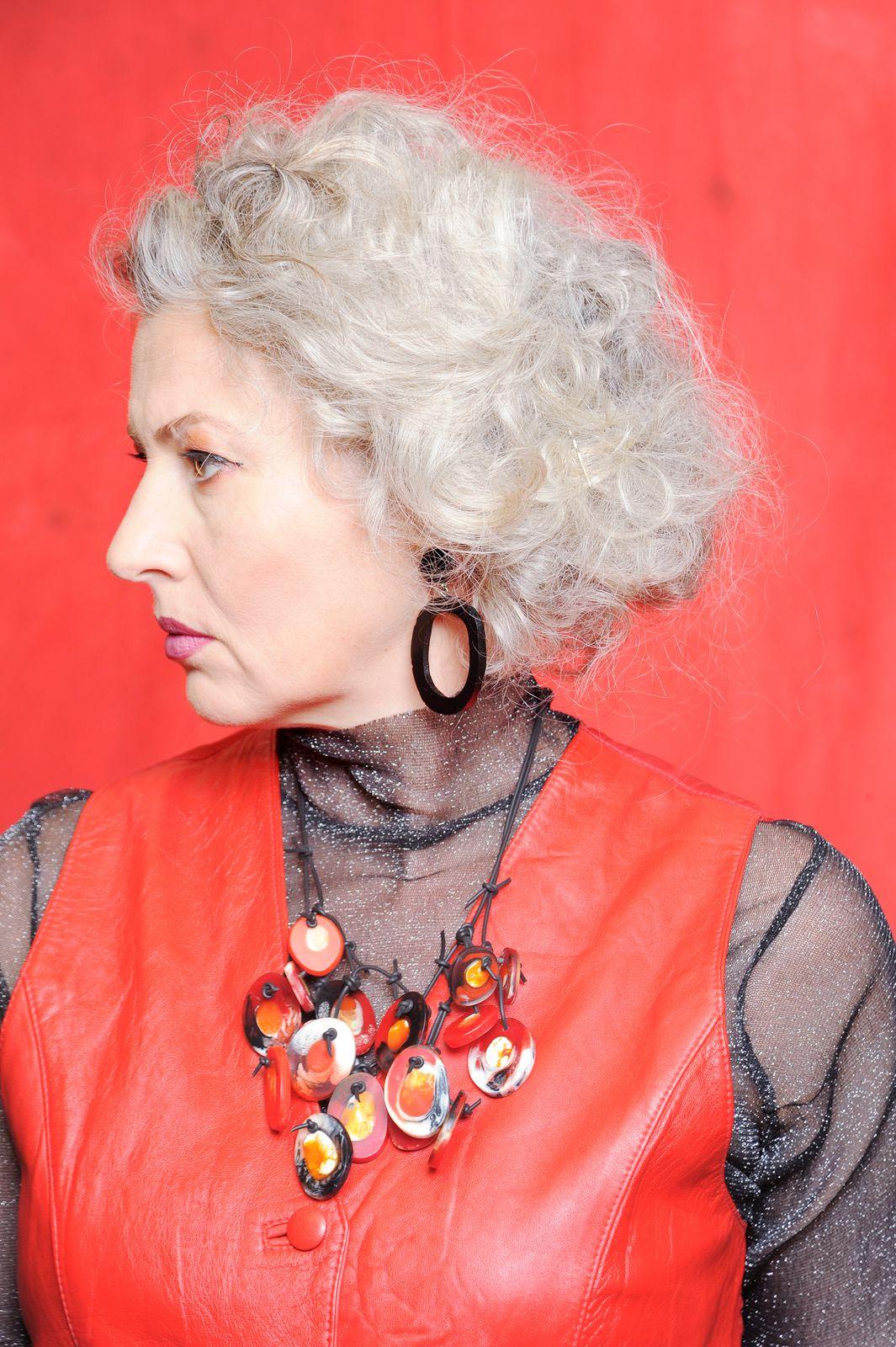 Die Schöpferin trägt ihr Machwerk: neu erfundene, rote Kunstharzkette