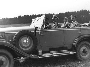 Erich Kempka - Erich Kempka au volant conduit Adolf Hitler (deuxième banc à la droite), Benito Mussolini (deuxième banc à la gauche) et le général Friedrich Hossbach (troisième banc). Les trois sont en mission d'observation de manœuvres de la Wehrmacht.