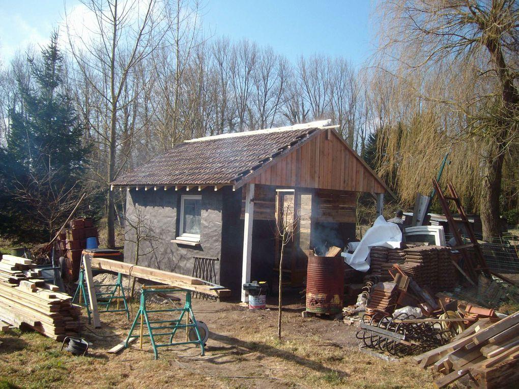 Trois photos pour illustrer le début de la construction de la cabane. Un cadre est fixé sur des fondations de béton. On habille le cadre.On place une grosse poutre au milieu, elle soutiendra les chevrons. Les suite ce sera pour la prochaine fois.