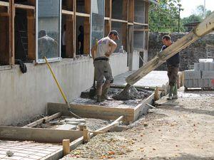 Vendredi 19 septembre 2014 : début des travaux.  Les maçons ont fait une tranchée avec la mini-pelle. Ils ont coulé du béton avec le camion toupie.  Un camion a amené des parpaings. Ils ont mis des parpaings dans la tranchée et fait deux murs à l'intérieur.  Ils ont coulé du ciment devant. Le maçon a étalé avec la règle et a lissé.