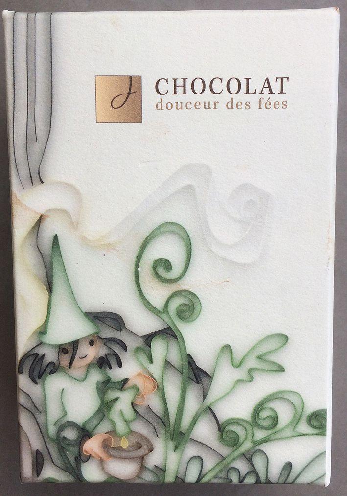 """""""La douceur des fées"""" contient un intérieur """"ganache"""" de chocolat noir traditionnel à base de crème fraîche et d'absinthe étendu entre deux couches fines de massepain pistaches et enrobé dans un chocolat blanc sur lequel est posé un décalque de la petite fée verte, icône de la région. Chocolaterie Jacques Perroud à Neuchâtel. Coll. Delahaye."""