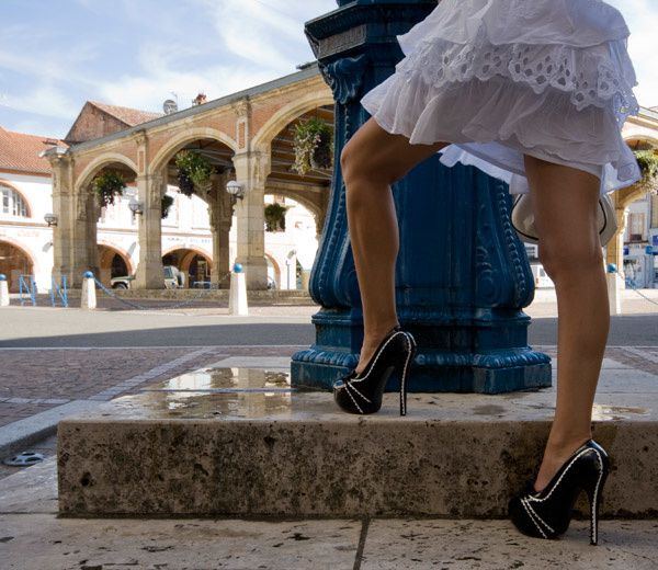 Lescarpin dévoile ses jambes gaînées de bas nylon et chaussée d'escarpins à talons hauts