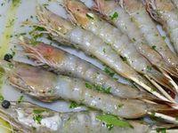 2 - Préparer une marinade dans un récipient refermable avec de l'huile d'olive, le jus d'une moitié de citron vert, le persil plat ciselé, le poivre de Timut, le sel, bien mélanger. Oter la carapace des gambas en laissant la tête et la queue et les placer dans la marinade en les badigeonnant bien. Laisser mariner pour 30 mn.