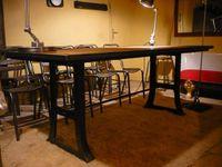 Table avec pieds en fonte - plateau latté en chêne ancien - encadrement métallique.