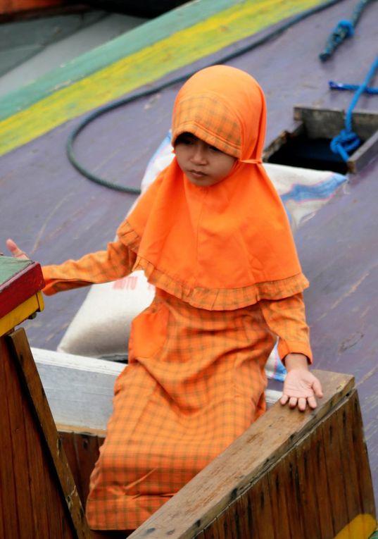 """""""Mettre les voiles"""", c'est voyager et souvent  le voile - qui veut cacher - révèle la lumière qui tombe sur le visage et la silhouette des Indonésiennes de tout âge, traversant le ponton."""