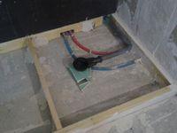 Le coffrage qui cachera la plomberie qui est en déport du placo et qui servira pour poser les produits de douche, et la pose de lambourdes et présentation de la bonde et évacuation avant de coller..
