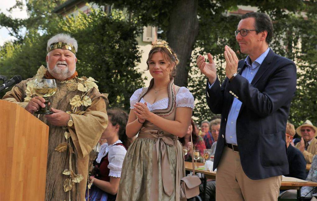 """Ein Loblied auf den Frankenwein kredenzte die örtliche Bacchus-Symbol-Figur alias Oswald Bamberger mit einem Gedicht: """"Als einst ich, Weingott Bacchus durchstreift die weite Welt, da war ich auch in Franken, wo es mir gut gefällt. So kam ich in ein Dörflein, gelegen schön am Main, es war die schöne Perle namens Veitshöchheim. Ein Weinfest wird gefeiert im schönen Frankenland, feudal mit Schloss und Garten, ein Paradies ich fand. Umgeben sind die Hänge mit edler Rebenpracht, dazu das schmucke Dörflein, wie mir das Freude macht. So kenne ich jetzt Franken und lass mir schenken ein, ich möchte ja probieren den guten Frankenwein. Ich freue mich zu feiern mit Gästen nah und fern, mit gutem Wein und Brotzeit da sitz ich bei euch gern. So bin ich ganz entzücket der Wein ist wirklich gut, Geschmack und Duft sind herrlich, er geht ganz stark ins Blut. Die Gäste sind gekommen der Wein macht alle froh, die Wirte sind zufrieden ihr Leut macht weiter so. Wer immer kommt nach Franken und kehrt mit Freude ein, dem wecken Wohlgefallen das Land, die Leut und der Wein."""""""