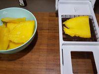 1 - Peler la mangue, la découper pour ôter le noyau et la tailler en petits cubes au couteau ou avec un appareil à trancher. Mettre quelques noisettes de beurre dans une poêle et y faire revenir les dés de mangue. Ajouter l'extrait de vanille, le sucre, laisser légèrement caraméliser et compoter sur feu doux jusqu'à obtenir une purée. Verser dans un bol et laisser refroidir.