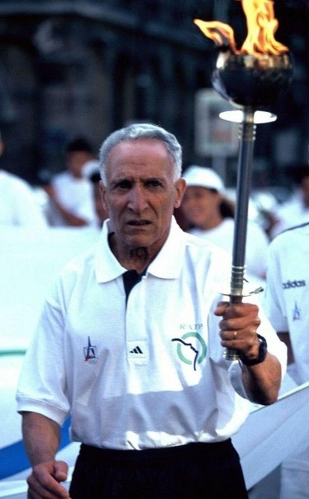 Alain Mimoun en 1994 et la flamme olympique, lors de la cérémonie d'ouverture du Congrès du Centenaire du CIO à Paris.