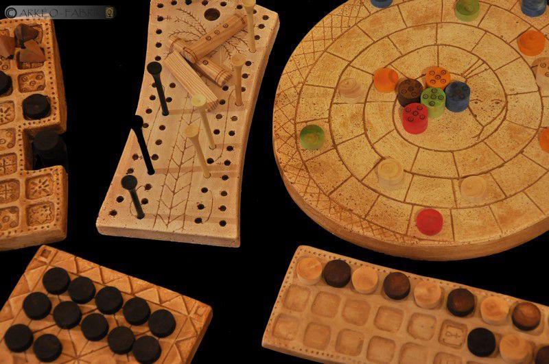 Différents plateaux de jeux, pions et dés contenus dans la mallette.