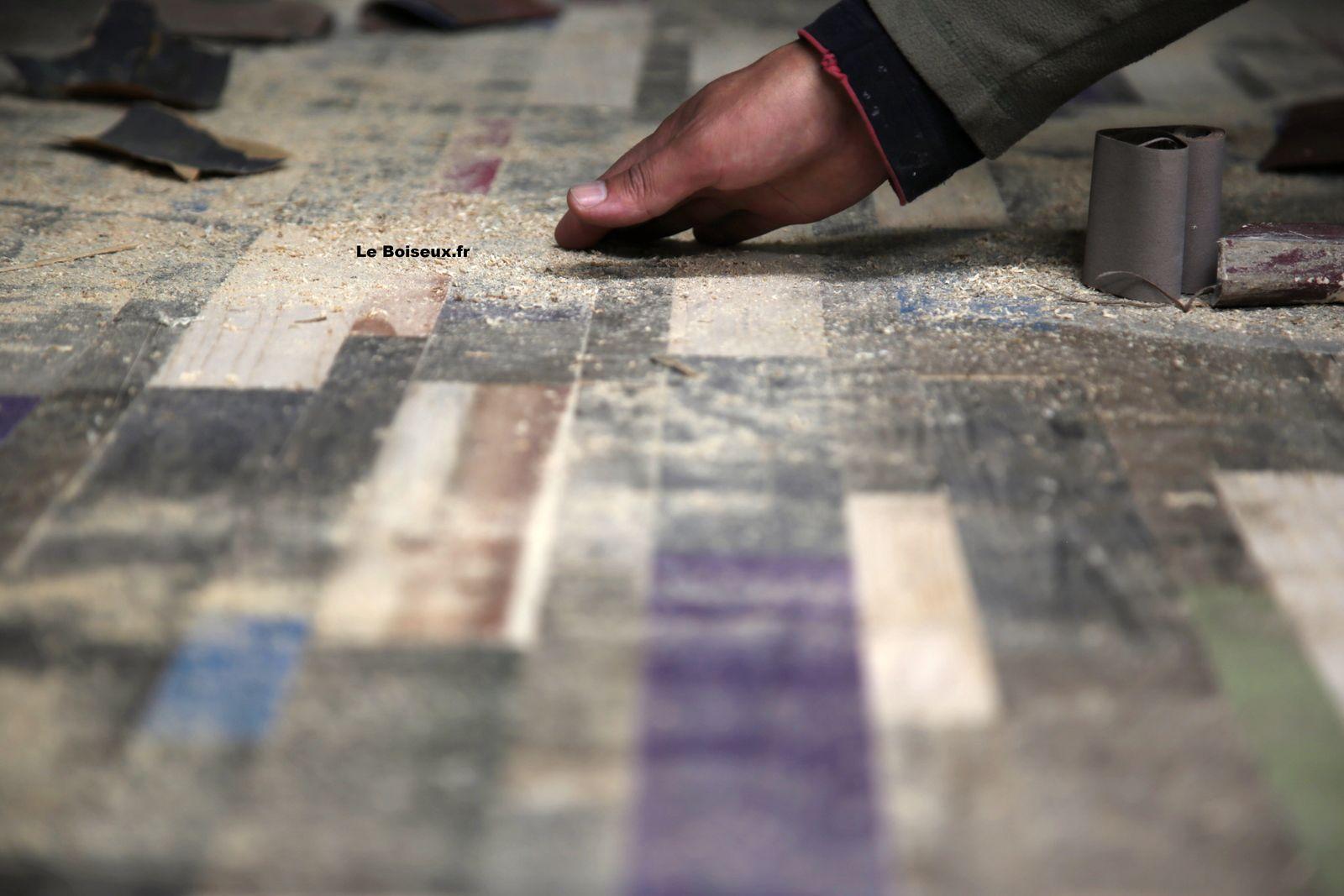 Le bout de ses doigts examine les aspérités du matériau, mesure les désaffleurs et les irrégularités, les recense, en évalue l'ampleur.