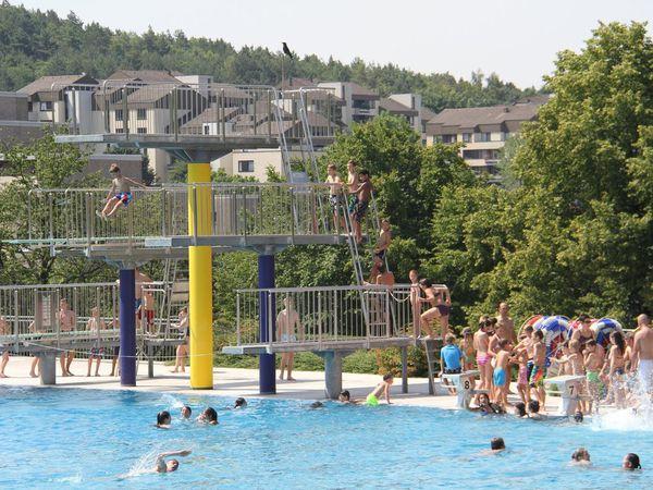 Für Farbtupfer in verkehrsgelb, nachtblau und signalrot sorgen die aus den Wasserflächen herausragenden Attraktionen wie Riesen- und Breitwellenrutsche und Sprungturm.