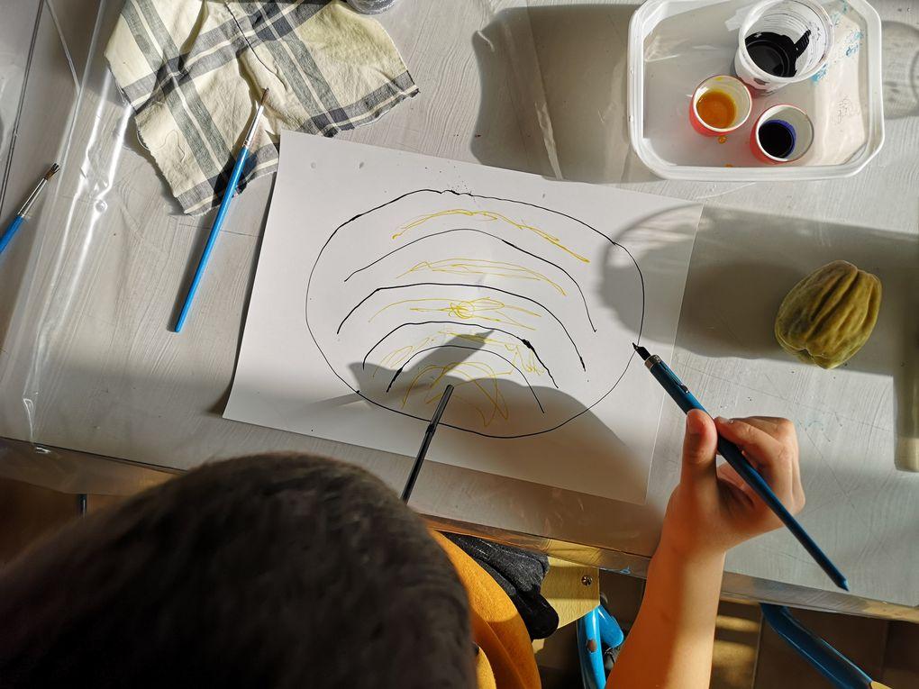Les enfants dessinent des graines à l'encre sur du papier photo et les découpent.