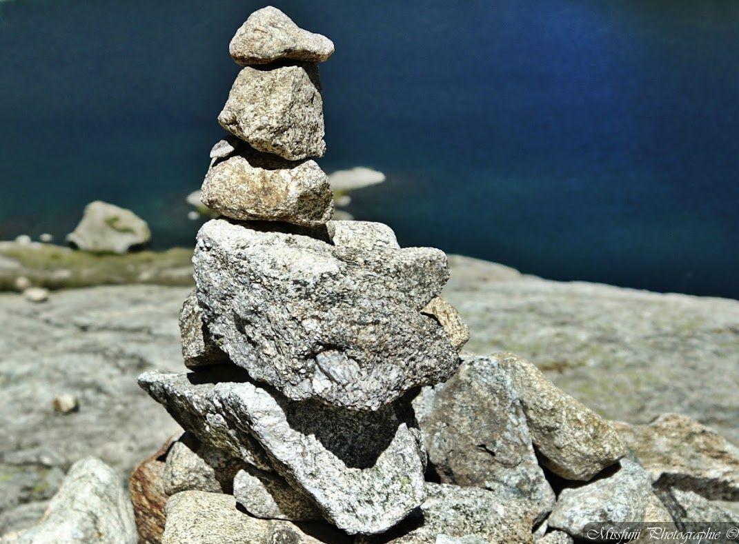 Voici ce que j'ai choisi pour illustrer le thème de ce samedi. Il s'agit d'une photographie que j'ai prise cet été au bord d'un lac dans la Vallée des Merveilles. Elle représente un monticule de pierres fait par l'homme et formés de pierres que l'on appelle des cairns. Ils font partie intégrante du balisage dans beaucoup d'itinéraires de randonnée. Ils servent à indiquer le chemin à suivre dans les endroits où un balisage ne serait pas pratique ou voyant. Ils servent de balisage dans les endroits qui peuvent avoir une visibilité réduite à cause du brouillard ou des intempéries. Enfin il indiquent le chemin à suivre là où le chemin n'est pas visible au sol car celui-ci est rocailleux. Mais ils sont aussiutilisés pour surveiller le niveau d'eau des rivières.