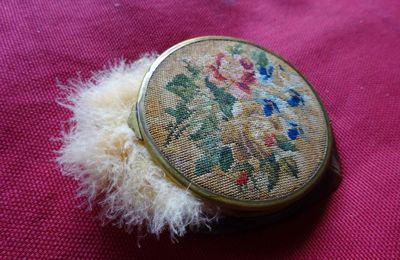Un poudrier ancien avec des fleurs  dessus, poudre & houppette dedans